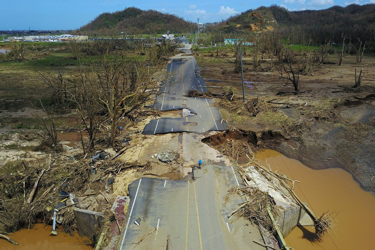 A man rides his bicycle through a damaged road in Toa Alta, west of San Juan, Puerto Rico, on September 24, 2017. RICARDO ARDUENGO/AFP/Getty Images
